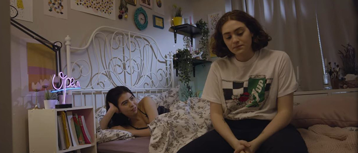 A young woman sits pensively at the edge of her bed, while another woman lies in the bed speaking to her.