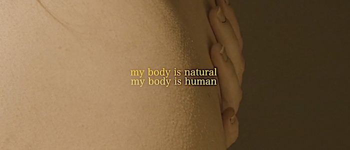 a hand caresses skin with the text my body is natural my body is human